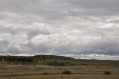 在冷的秋天天空的重的灰色云彩在河、领域、森林和山 免版税库存照片
