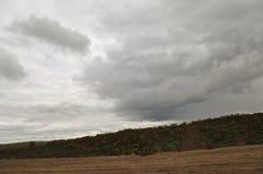 在冷的秋天天空的重的灰色云彩在河、领域、森林和山 库存照片