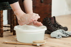 在冷的肥皂的水和刷子的卷起的脚趾 免版税库存照片