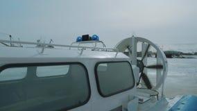 在冻河的小气垫船有运转的推进器和蓝色光的 影视素材