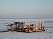 在冻河的未完成的结构冬天城市背景的日落的 免版税库存照片
