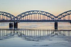在冻河的铁路桥在太阳期间的多雪的冬天里加 库存图片