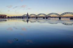 在冻河的铁路桥在太阳期间的多雪的冬天里加 免版税库存照片