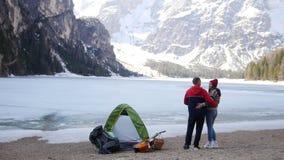 在冻湖和享受山看法海岸的年轻拥抱的夫妇身分  影视素材