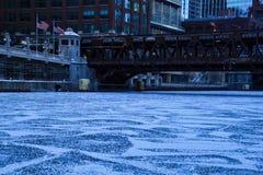 在冻芝加哥河的低角度视图的破裂和积雪的冰在一个蓝色和寒冷早晨 免版税库存照片