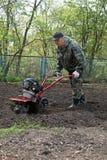在准备地面耕地机的庭院里供以人员工作 免版税库存图片
