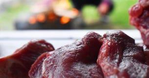 在准备好木的桌上的新鲜的未煮过的红肉被烹调在室外火格栅 烤肉在庭院里 免版税库存图片