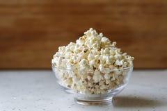 在准备好的玻璃碗的新鲜的热的玉米花被吃 图库摄影