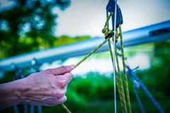 在准备好筏的绳索的Globed手航行 免版税库存照片