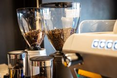 在准备的磨咖啡器的烤咖啡豆研咖啡,行业电研磨机在咖啡馆商店 免版税库存照片