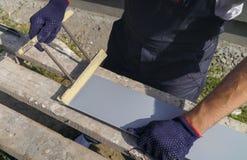 在准备PVC窗口基石与剪刀特写镜头的防护手套的工作者手切口金属 免版税库存照片