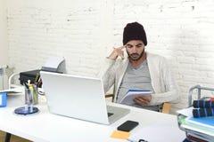 在凉快的行家童帽文字的时髦商人在运转在有计算机的现代家庭办公室的垫 库存照片