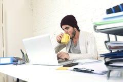 在凉快的运作在有计算机的现代家庭办公室的行家童帽饮用的咖啡的时髦商人 免版税库存照片