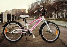 在减速火箭式的妇女的自行车,白色与桃红色条纹 免版税库存照片