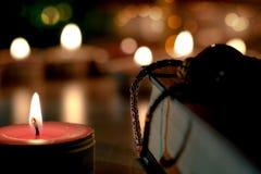 在减速火箭的圣经的祷告和希望概念由蜡烛光点燃了 免版税库存图片