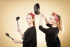 在减速火箭的女孩之间的厨房战斗 免版税库存图片