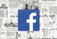 在减速火箭的报纸背景安置的Facebook象 库存照片