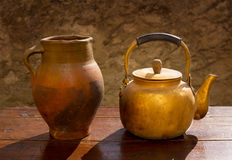在减速火箭的木桌上的古色古香的黄铜茶壶和黏土刺激 免版税图库摄影