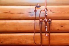 在减速火箭的样式的古铜色明三联式浴缸水嘴在日志墙壁上在公共浴室 库存图片