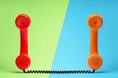 在减速火箭的样式的红色和橙色电话 库存照片