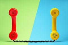 在减速火箭的样式的红色和黄色电话耳机 库存图片