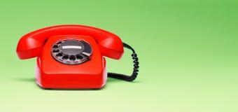 在减速火箭的样式的红色电话在绿色背景 图库摄影