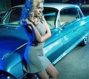 在减速火箭的汽车旁边的聪明的妇女 免版税图库摄影