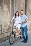 在减速火箭的纵排自行车的年轻夫妇在街道城市 库存图片