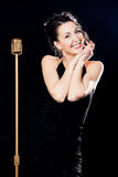 在减速火箭的话筒后的微笑的妇女歌手 免版税图库摄影