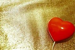 在减速火箭金的背景的红色心脏 免版税库存图片