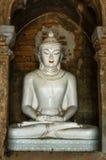 在凝思姿势的白色菩萨大理石与金黄三只眼 免版税库存照片