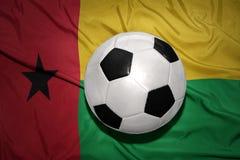 在几内亚比绍的国旗的黑白橄榄球球 免版税库存照片