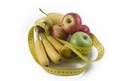 在几新鲜水果附近被包裹的测量的磁带 免版税库存图片