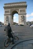在凯旋门附近的骑自行车者地方的夏尔・戴高乐在巴黎 免版税库存照片