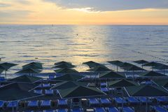 在凯梅尔使与伞的sunbeds和日出靠岸 免版税库存照片