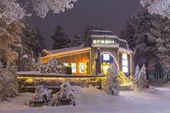 在出租办公室前面的雪上电车在罗瓦涅米村庄 库存照片