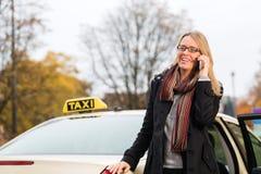 在出租汽车前面的少妇有电话的 图库摄影