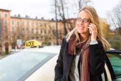 在出租汽车前面的少妇有电话的 库存图片