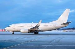 在出租汽车的乘客飞机在溜滑冰冷的沥青的冬天 免版税库存照片