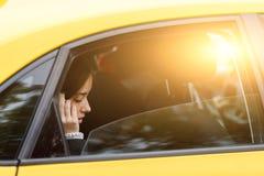 在出租汽车的妇女骑马和谈话与某人电话的 免版税库存照片