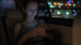 在出租汽车的年轻成年女性使用巧妙的电话