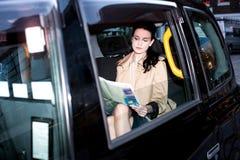 在出租汽车里面的女性乘客读书报纸 库存图片