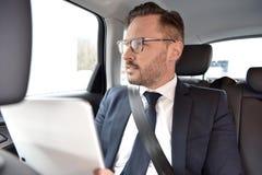 在出租汽车读书新闻的商人 免版税图库摄影