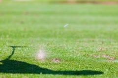 在击中球的高尔夫球运动员以后的草飞溅 免版税库存照片
