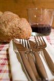 在刀叉餐具上添面包 免版税图库摄影