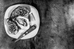 在刀子和柠檬陪同的一块白色板材的牡蛎在黑白 免版税库存图片
