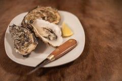 在刀子和柠檬陪同的一块白色板材的牡蛎 免版税图库摄影