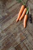 在刀子旁边的三棵红萝卜 免版税图库摄影