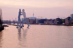 在分子人雕塑的看法在日出 柏林,德国- 库存图片