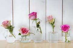 在分开的玻璃花瓶的五朵玫瑰 免版税库存图片
